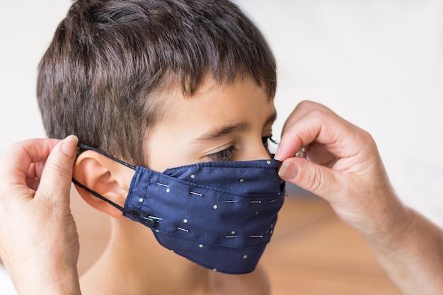 Criança marrom de perfil que está sendo testada com uma máscara azul