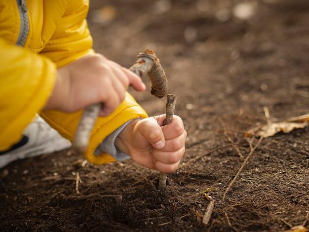 Criança martelando com varas com jaqueta amarela. se divertindo na floresta. criança brincando com sujeira.