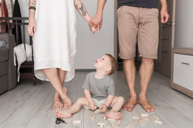 Criança masculina que joga com blocos de madeira que olha o par que prende a mão de cada um