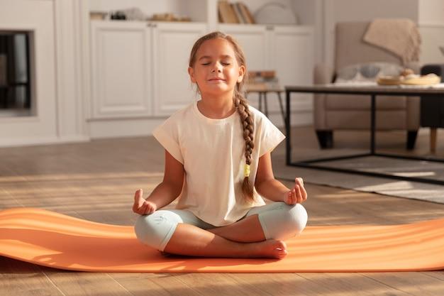 Criança meditando no tapete de ioga, tiro completo