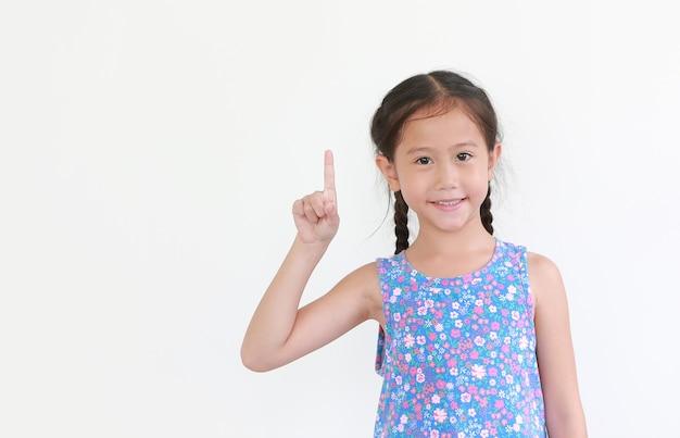 Criança menina asiática apontando o dedo indicador isolado no branco