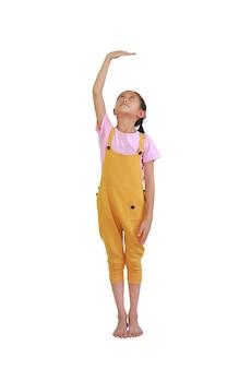 Criança menina asiática mede o crescimento isolado sobre fundo branco. criança calcula sua altura com a mão