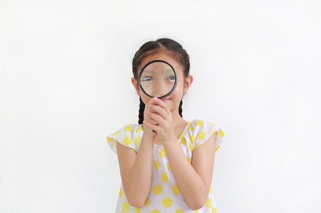 Criança menina asiática olhando através de uma lupa sobre fundo branco