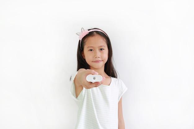 Criança menina asiática segurando o controle remoto isolado no fundo branco.