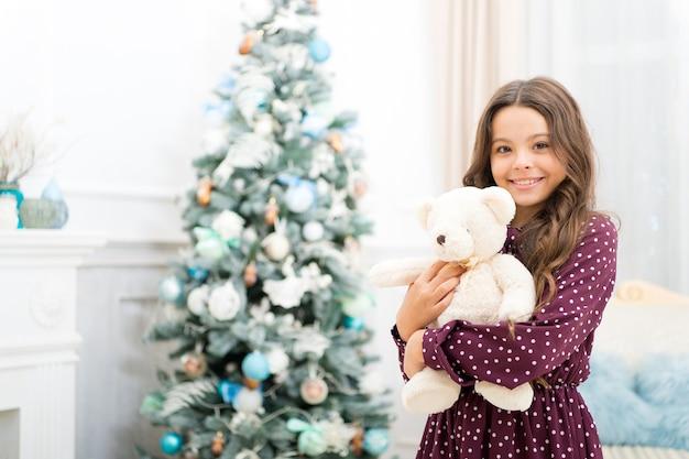 Criança menina bonitinha com presente de natal. na manhã antes do natal. esperando o papai noel. inverno. feliz ano novo. compras de natal. férias de natal em família. por deus, seja alegre.