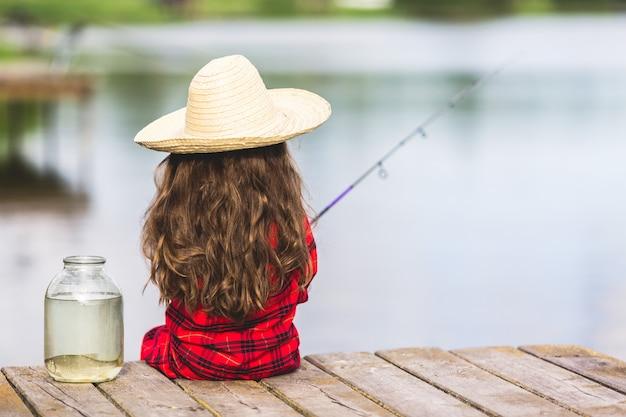 Criança menina bonitinha em botas de borracha e chapéu de palha pesca no cais de madeira perto de jarra de vidro e peixinho no lago