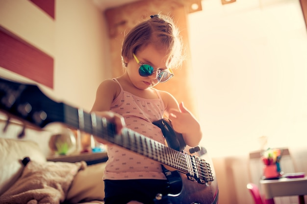 Criança menina bonitinha em óculos de sol tocando violão.
