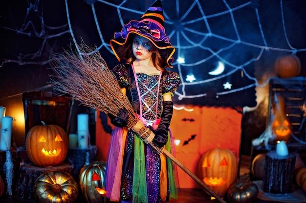 Criança menina bonitinha em uma fantasia de bruxa com vassoura mágica comemora em casa, em um interior com abóboras e casa mágica de papelão no fundo.