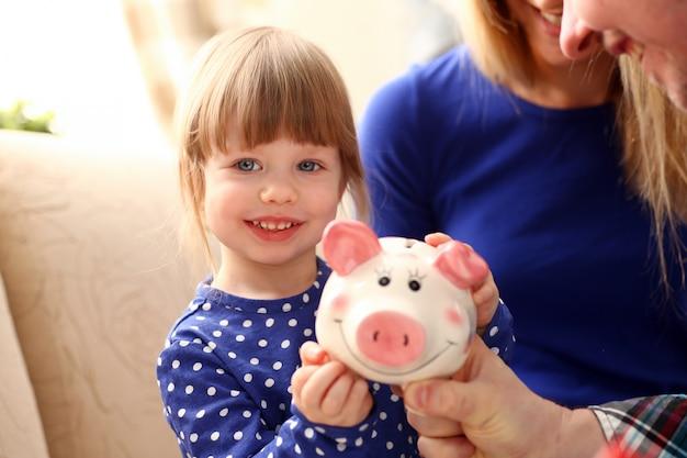Criança menina braço colocando moedas no piggybank