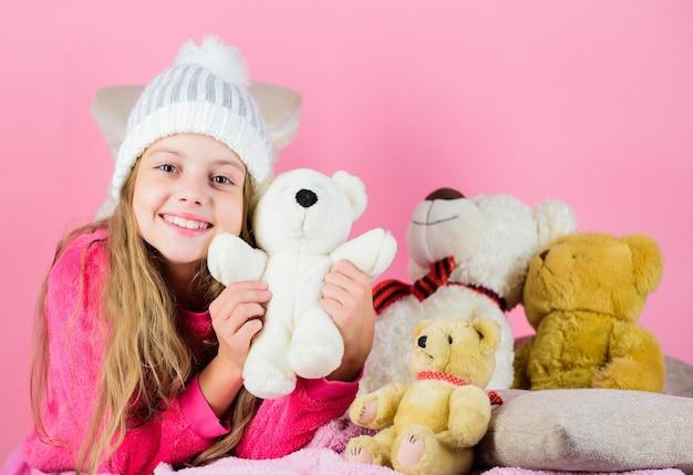 Criança menina brincar com ursinho de pelúcia de brinquedo macio em fundo rosa. coleção de brinquedos de ursos. criança pequena menina brincalhão segurar o ursinho de pelúcia brinquedo. os ursos de pelúcia ajudam as crianças a lidar com as emoções e a limitar o estresse.