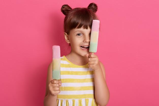 Criança menina caucasiana expressando felicidade, sustenta dois sorvetes e cobrindo os olhos com pirulitos de uma fruta, de pé contra a parede rosa, se divertindo no verão.