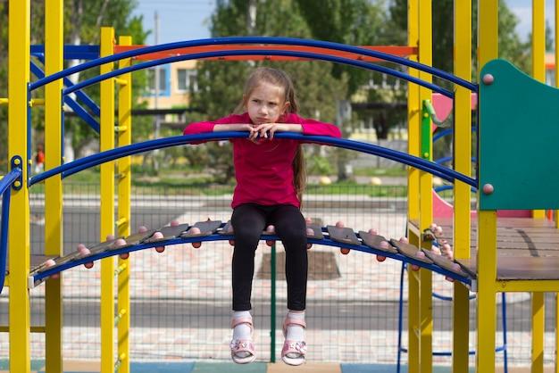 Criança menina com cabelo loiro em camiseta rosa está triste no parquinho sentada no escorregador com as pernas balançando