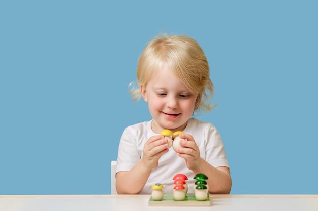 Criança menina de anos brinca com brinquedo educacional de classificação de madeira dentro de casa