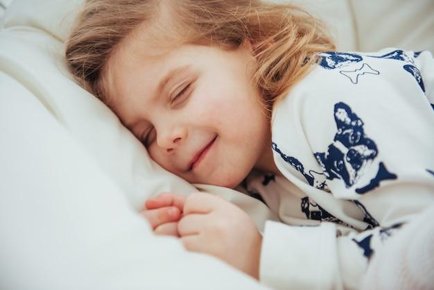Criança menina dorme na cama