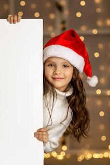 Criança menina feliz com chapéu de papai noel vermelho segurando banner de papelão branco em branco com espaço vazio