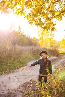 Criança menina feliz rindo e brincando no outono
