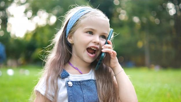 Criança menina feliz tendo uma conversa falando em seu sellphone no parque de verão.