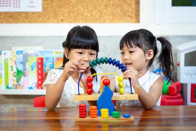 Criança menina jogando brinquedos de madeira
