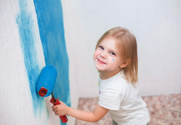 Criança, menina pinta uma parede de rolos em azul