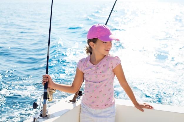 Criança menina velejando no barco de pesca, segurando a haste