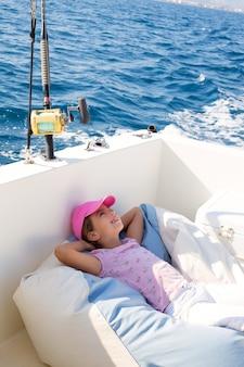 Criança menina velejando relaxado no convés do barco ejoying uma soneca