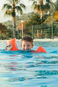 Criança menino bonitinho brincando na piscina em um dia quente de verão crianças aprendem a nadar criança feliz com flutuadores laranja proteção auxiliar de natação para criança férias familiares de verão