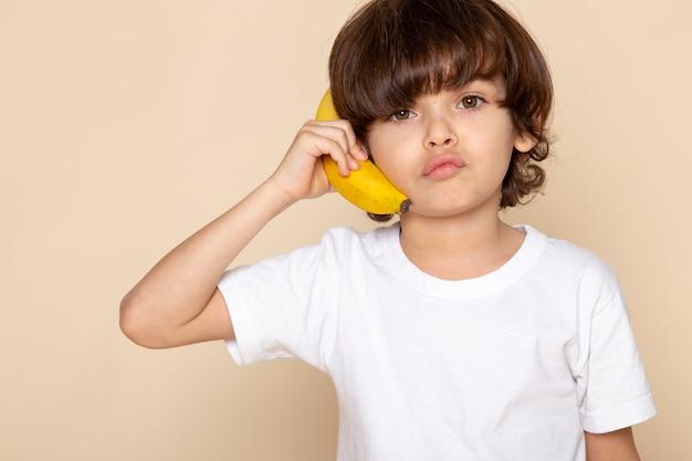 Criança menino bonito adorável em t-shirt branca com banana rosa