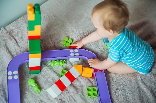 Criança menino criança brincando em casa em um conjunto de construção multicolorido jogos infantis em casa desenvolvimento infantil em jogos seguros de jogar