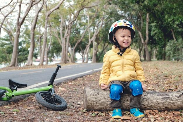 Criança menino criança usando capacete de segurança, sentado num tronco de madeira, dando um tempo depois de andar de bicicleta de equilíbrio