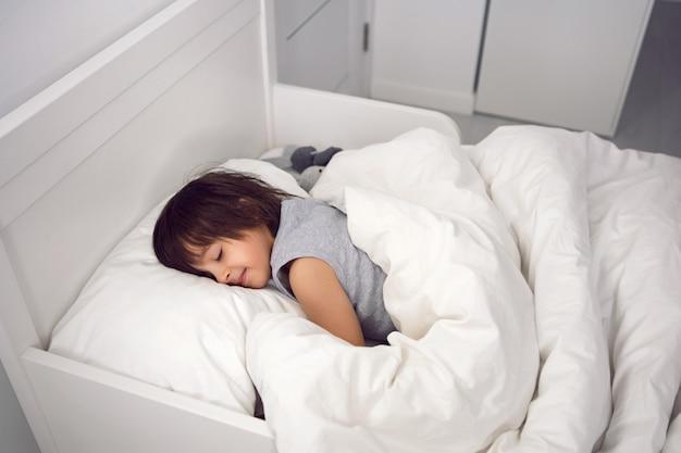 Criança menino deitado em uma cama infantil branca com um cobertor em um quarto com brinquedos de coelhos