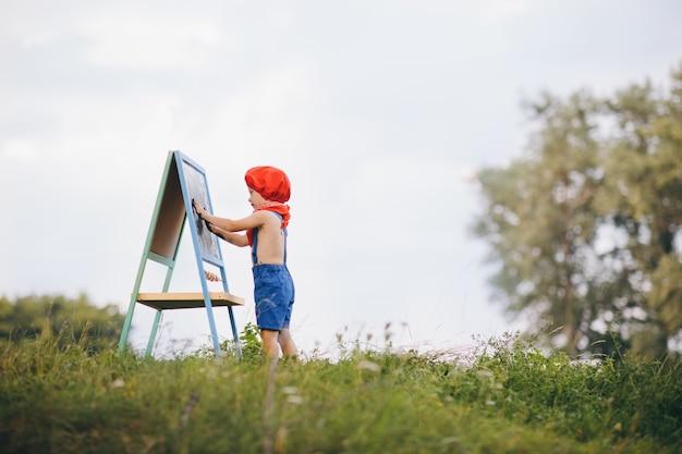 Criança menino desenho imagens ao ar livre no parque de verão