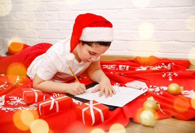 Criança menino escrevendo carta para o papai noel em casa apresenta lista de desejos