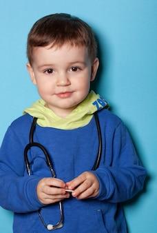 Criança menino feliz segurando estetoscópio sobre fundo azul como um médico