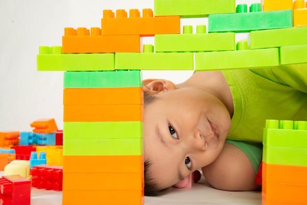 Criança menino jogando tijolo plástico bloco colorido com feliz