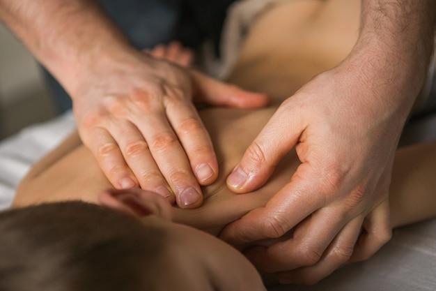Criança menino relaxa de uma massagem terapêutica. fisioterapeuta, trabalhando com o paciente na clínica, nas costas de uma criança