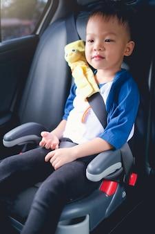 Criança menino sentado no assento do carro