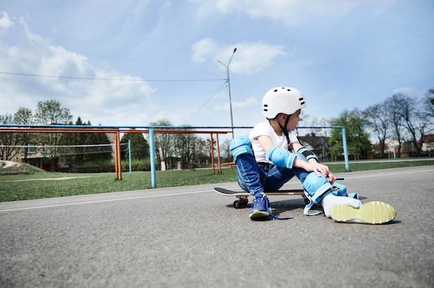 Criança menino skatista olhando para longe enquanto está sentado em um skate e vestindo equipamento de proteção
