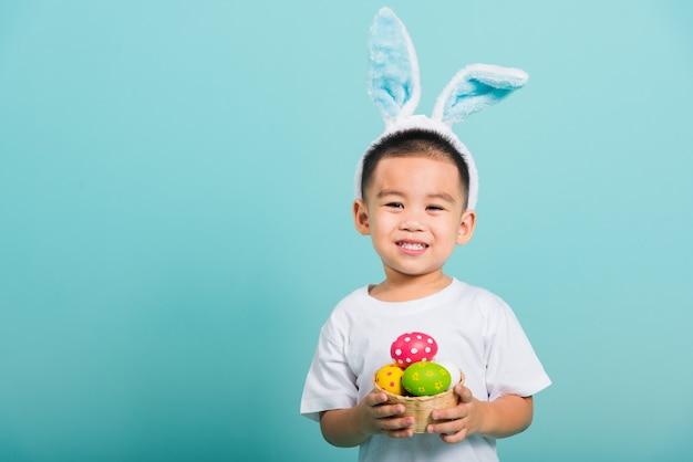 Criança menino sorrir usando orelhas de coelho e camiseta branca, segure a cesta com ovos de páscoa completos
