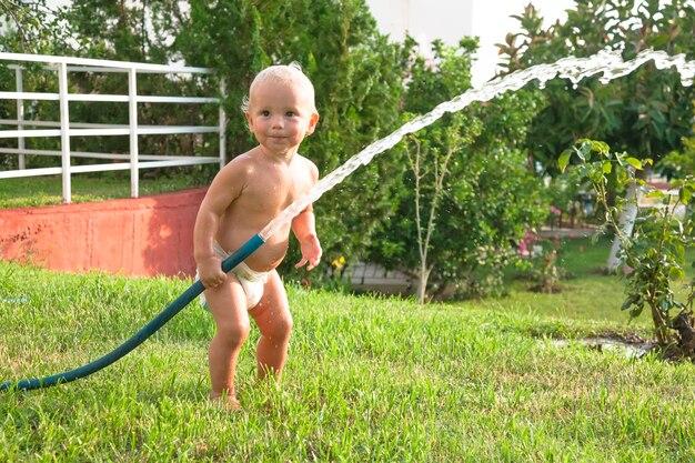 Criança molhando a grama no quintal