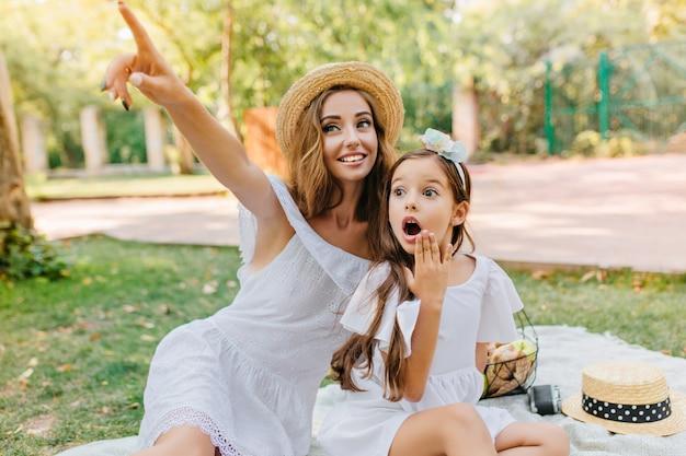 Criança morena de cabelos compridos posando com expressão de rosto chocado na natureza. mulher jovem deslumbrante em um traje branco e chapéu vintage olha para algo interessante e apontando com o dedo.