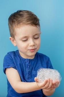 Criança mostrando as mãos com espuma de sabão, conceito de limpeza e higiene. limpar as mãos com água e sabão ajudará a evitar uma epidemia de vírus pandêmico
