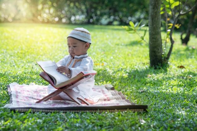 Criança muçulmana asiática está lendo o alcorão no parque, conceito de islamismo,