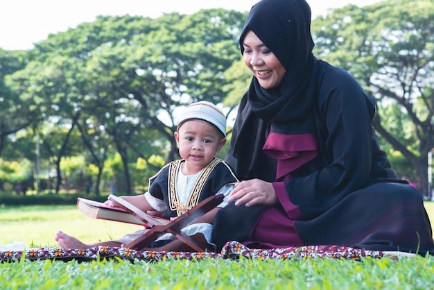 Criança muçulmana asiática está lendo o alcorão no parque, mãe muçulmana e filho conceito