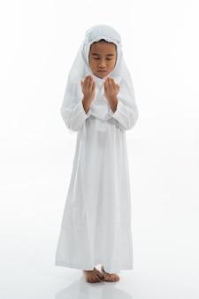 Criança muçulmana rezando e vestindo ihram