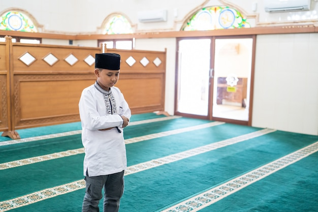 Criança muçulmana rezando na mesquita