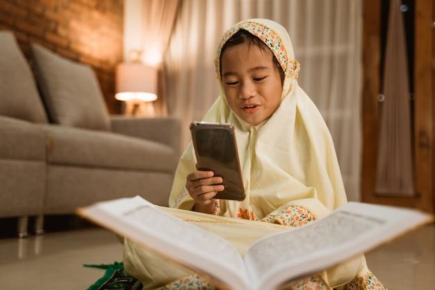 Criança muçulmana usando telefone celular depois de rezar