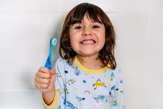 Criança muito alegre depois de escovar os dentes com uma escova de dentes com pijama antes de ir para a cama