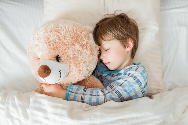 Criança na cama, feliz hora de dormir no quarto branco