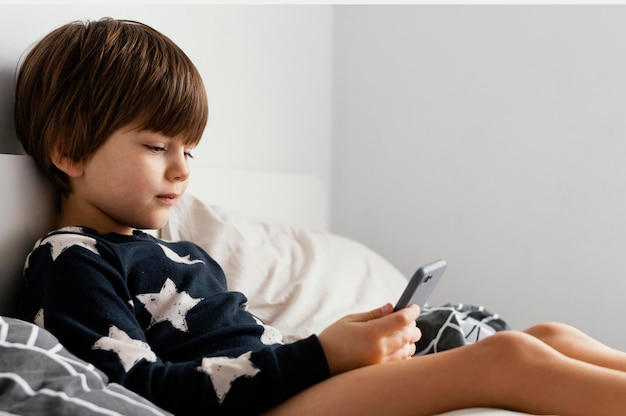 Criança na cama segurando smartphone