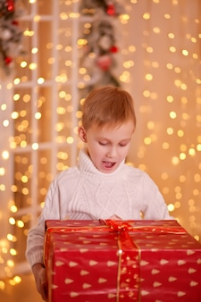 Criança na camisola de malha branca, segurando uma caixa de presente de natal nas mãos e abriu a boca em surpresa